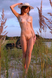 Nude girl in hat at the nature