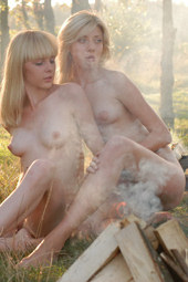 Two blondes nude in the forest by the fireplace
