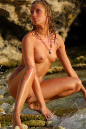 Playful young naturist in the forest river