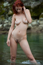 Busty redhead with hairy pussy is nude in the crystal clear lake