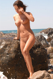 Big sea rocks and nude sexy brunette on them