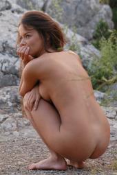 Beautiful brunette hottie is nude outdoor in stone jungle