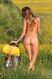 Cycling nude in the field full of yellow flowers