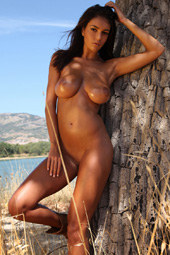Hot big boobs brunette is nude at the nature