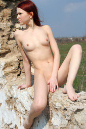 Redhead girl is nude outdoor on the rocks