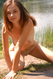 Young sexy naturist is at the forest lake